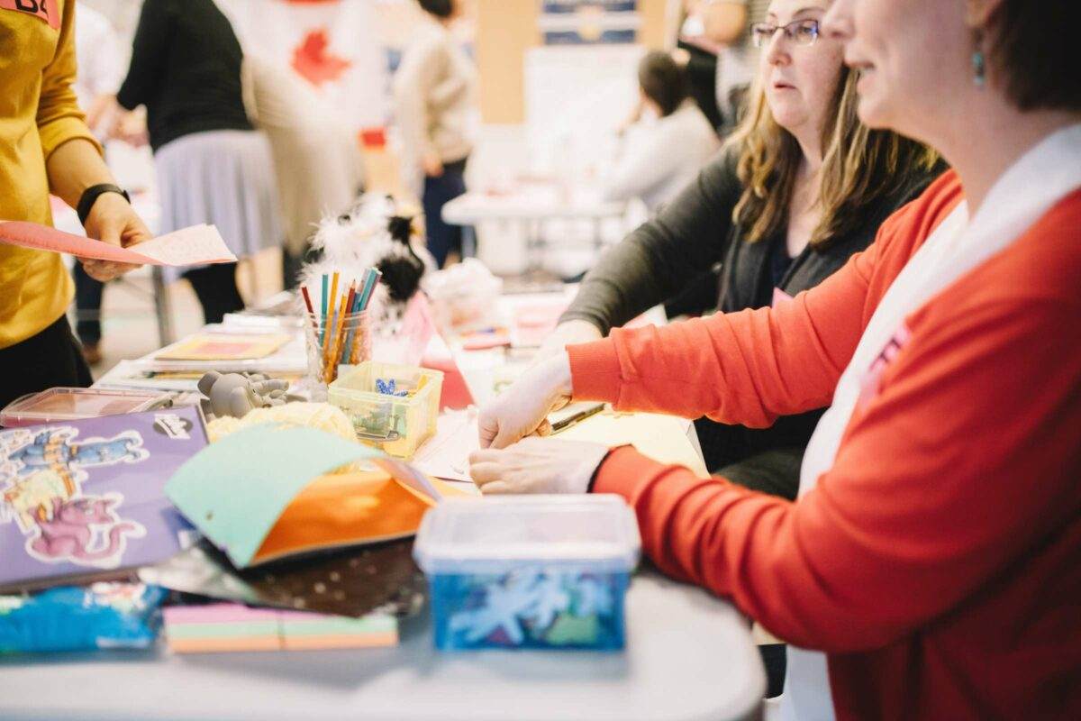 Participants sit at a table with workshop supplies
