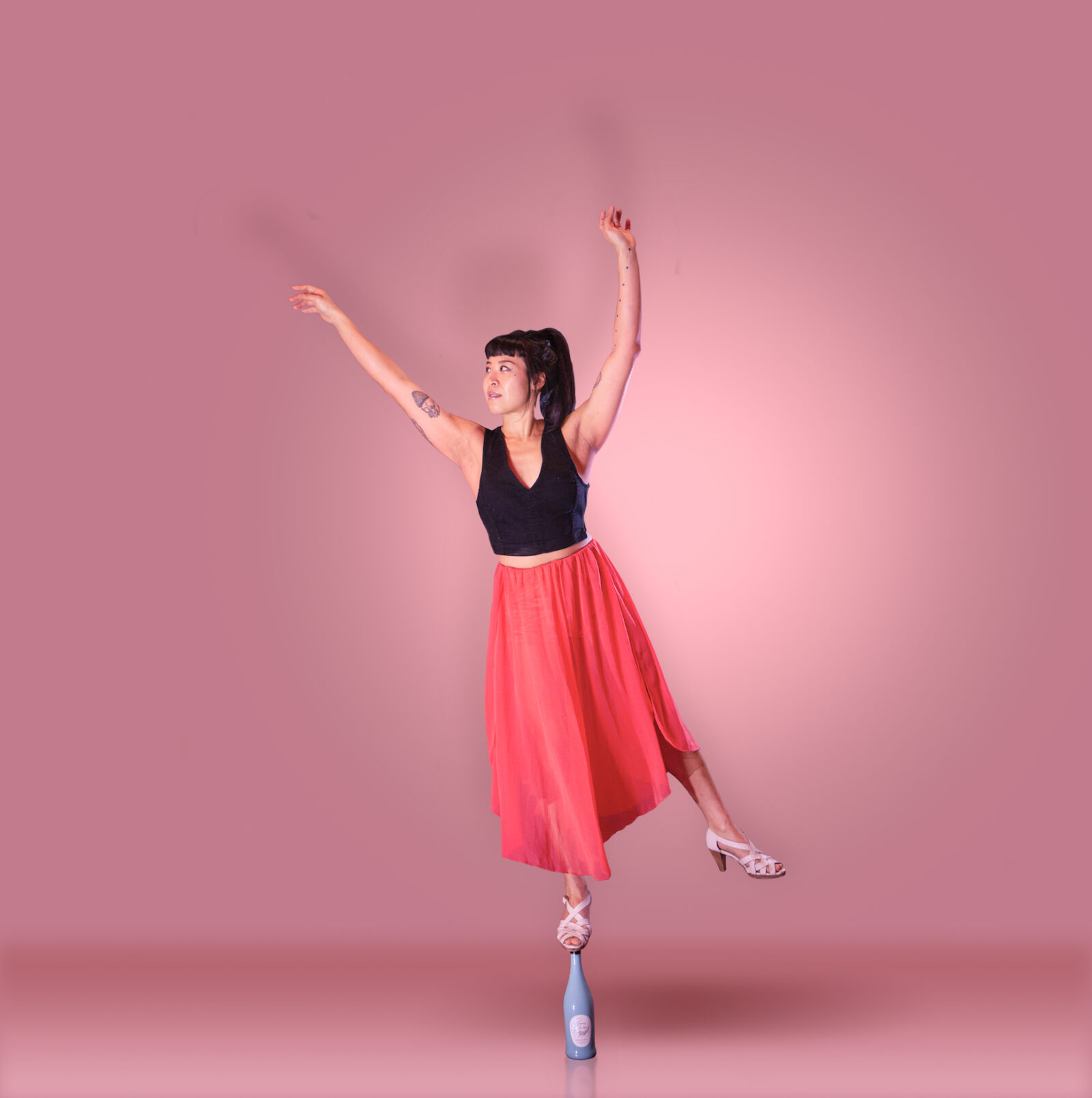 Renee balancing on a bottle posed against an all-pink backdrop