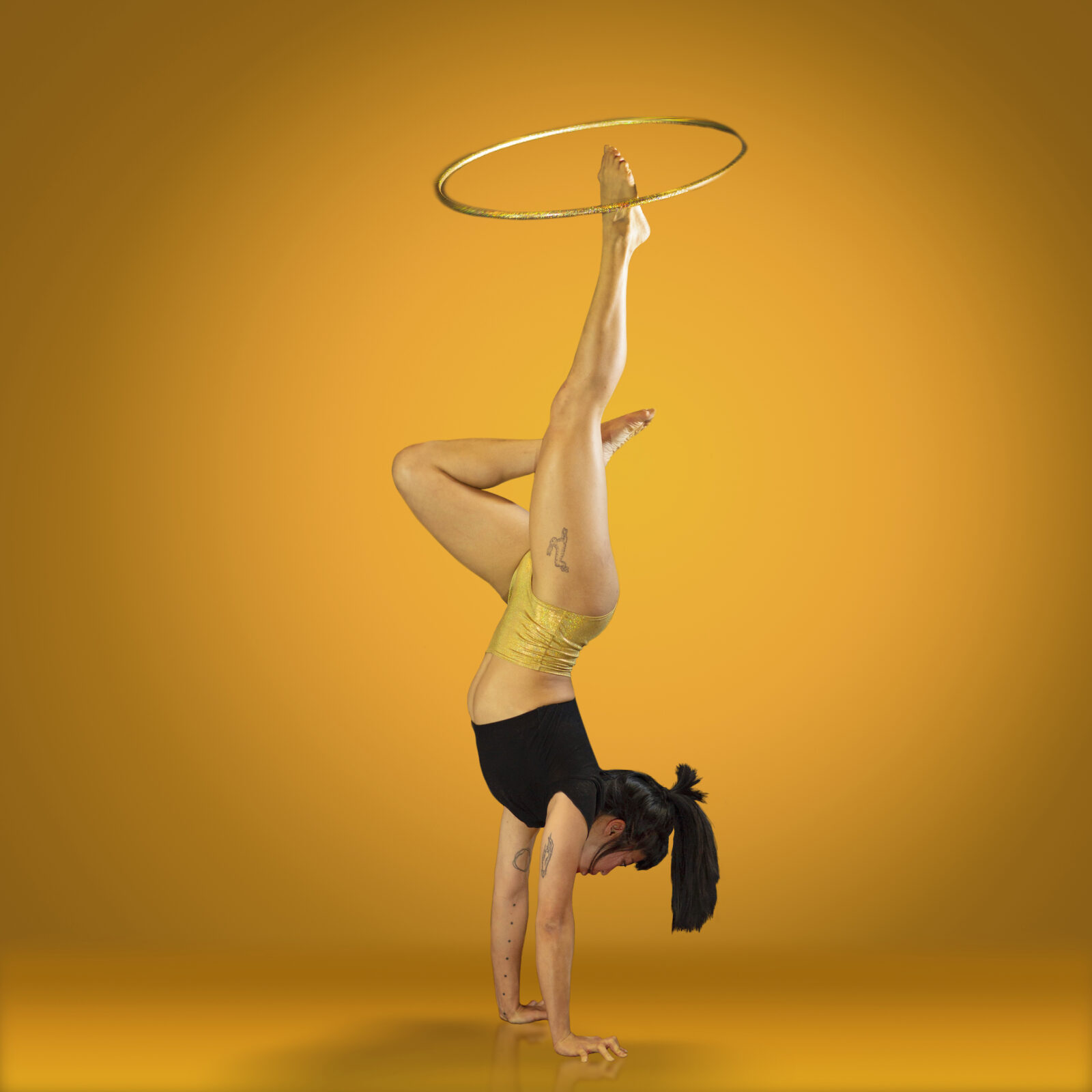 Renee doing a handstand while spinning a hula hoop on her foot
