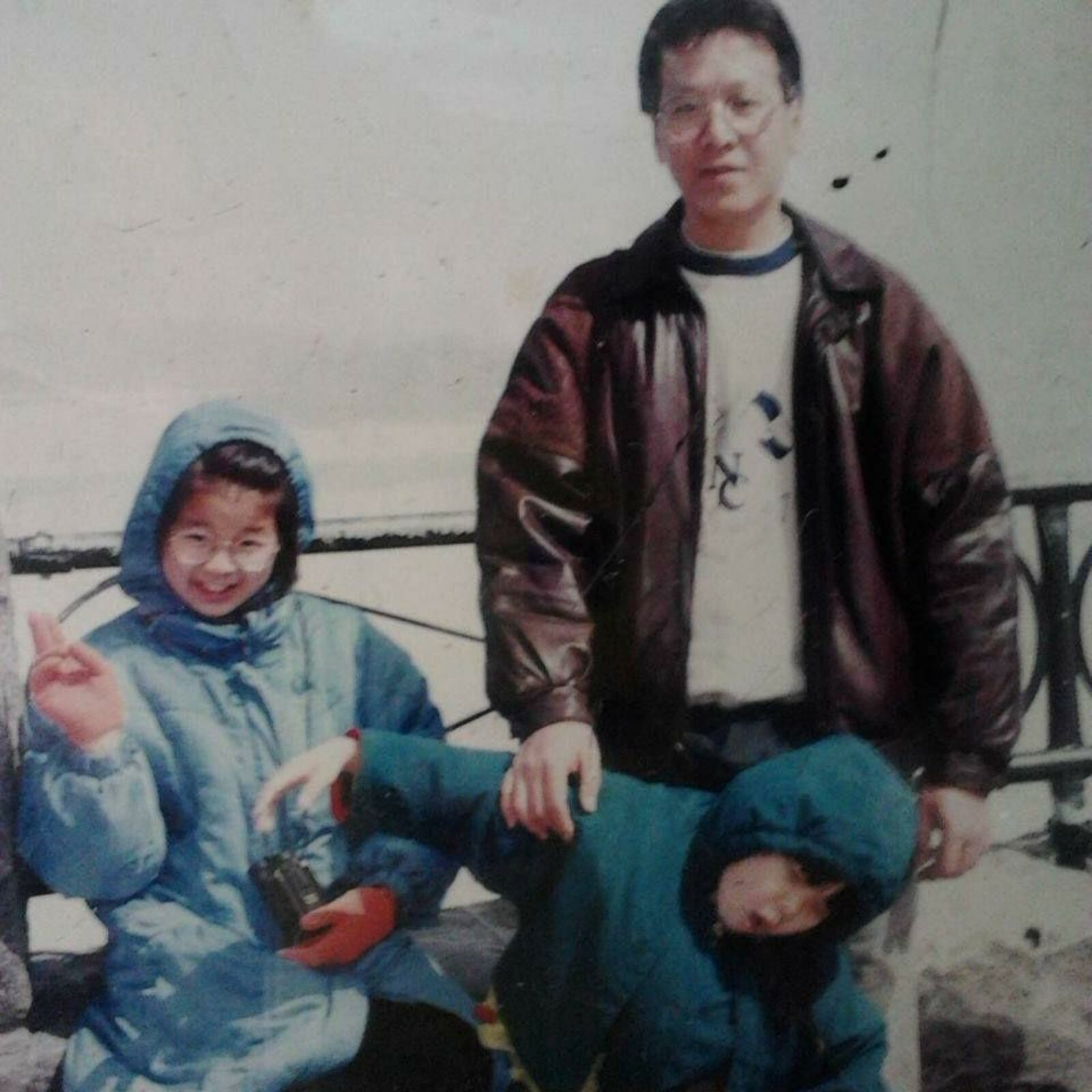 Renee as a child clowning around while her sister and father pose for a photo.